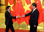 Chinese President Xi Jinping prepares to shake hands with Vietnamese President Truong Tan Sang before their meeting at the Great Hall of the People...