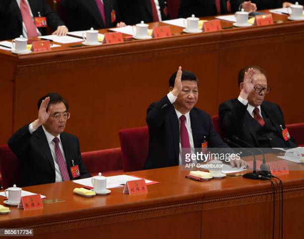 Chinese President Xi Jinping raises his hand to vote for the reports with China's former presidents Jiang Zemin and Hu Jintao at the closing of the...
