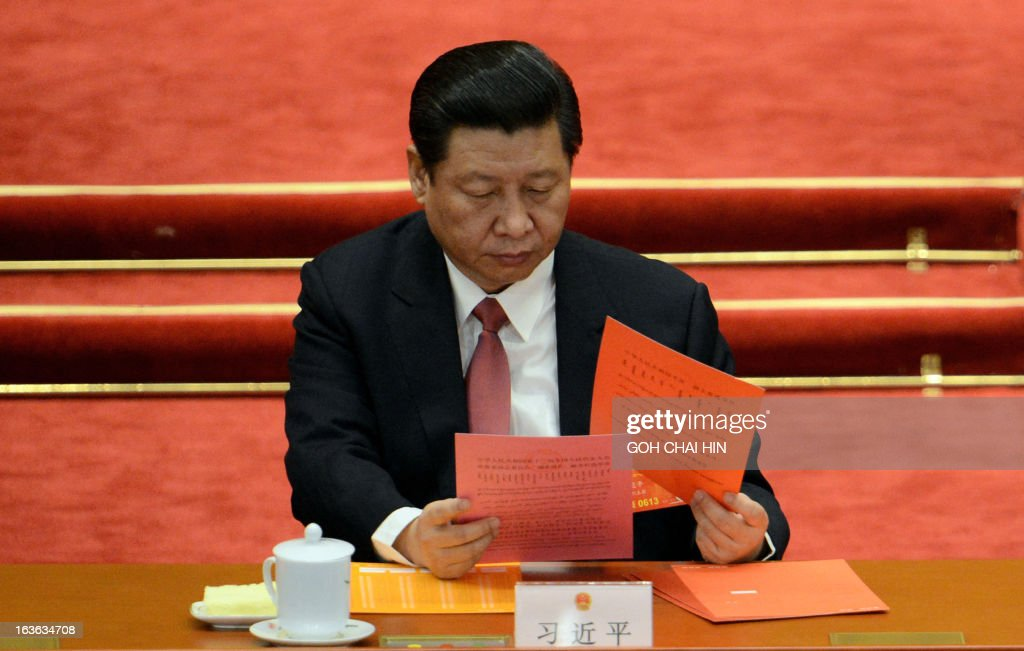 Chinese President Xi Jinping reads his ballot papers prior to the election for a new president of China during the 12th National People's Congress (NPC) in the Great Hall of the People in Beijing on March 14, 2013. China's parliament is to name Xi Jinping as the country's new president on March 14, formalising his leadership of the world's most populous nation four months after he took charge of the ruling Communist Party.