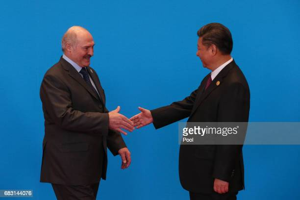 Chinese President Xi Jinping shakes hands with Belarus President Alexander Lukashenko as they attend the welcome ceremony at Yanqi Lake during the...