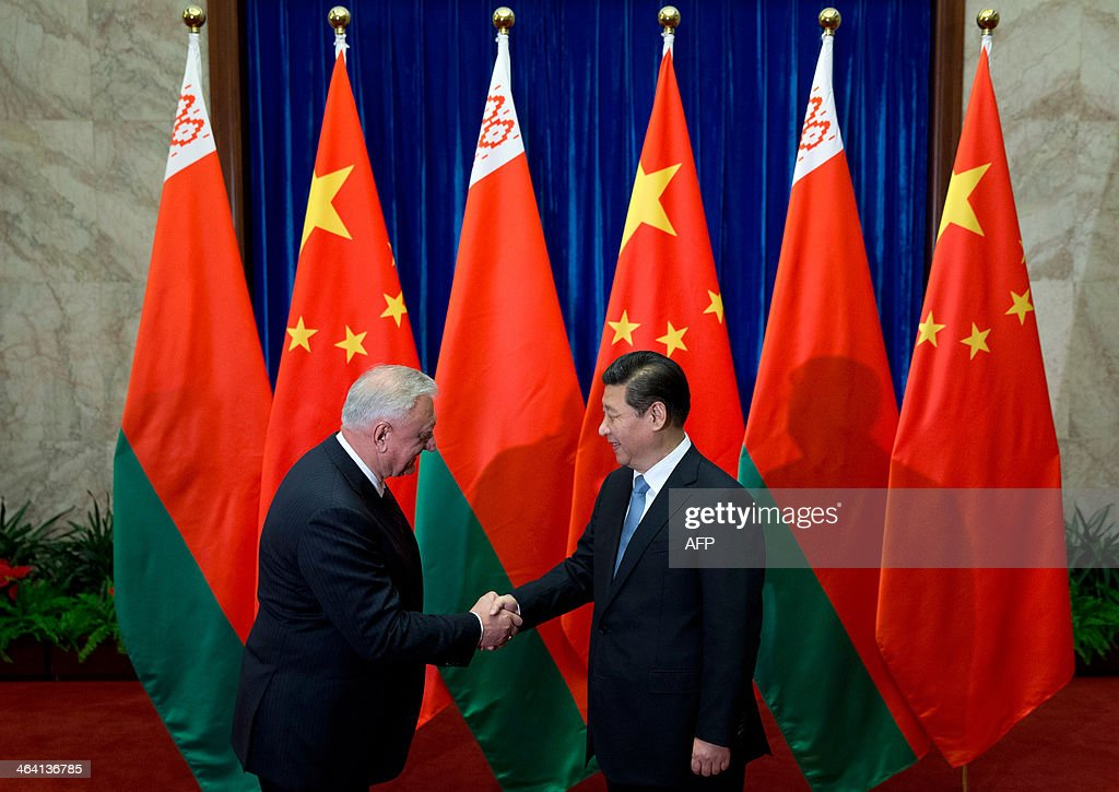 Chinese President Xi Jinping (R) shakes hands with Belarus' Prime Minister Mikhail Myasnikovich (L) before their meeting at the Great Hall of the People in Beijing on January 21, 2014. AFP PHOTO / Alexander F. Yuan / POOL