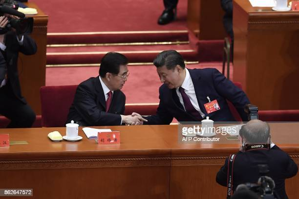 Chinese President Xi Jinping shakes hands with China's former president Chinese former president Hu Jintao at the opening session of the Chinese...