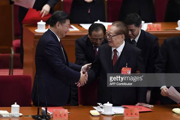 TOPSHOT Chinese President Xi Jinping shakes hands with China's former president Jiang Zemin during the closing of the 19th Communist Party Congress...