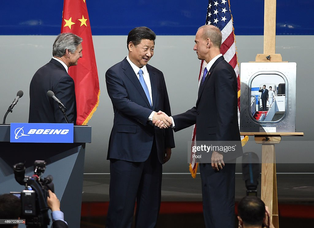 Chinese President Xi Jinping shakes hands with Dennis Muilenburg President and CEO of the Boeing Company and watched by Ray Conner President and CEO...