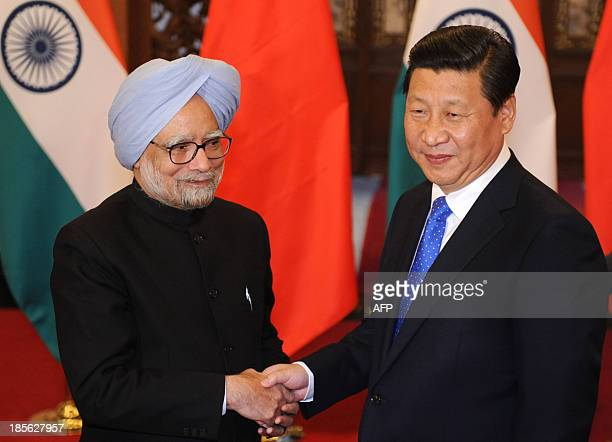 Chinese President Xi Jinping shakes hands with India's Prime Minister Manmohan Singh before their meeting at the Diaoyutai State Guesthousein in...