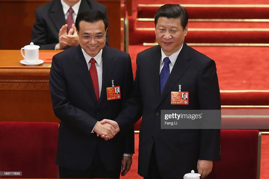 Chinese President Xi Jinping (C) shakes hands with newly-elected Premier Li Keqiang (L) as former Chinese Premier Wen Jiabao (R) looks on during the fifth plenary meeting of the National People's Congress at the Great Hall of the People on March 15, 2013 in Beijing, China. Li Keqiang was elected as China's Premier Friday at the 12th National People's Congress, the country's top legislature.