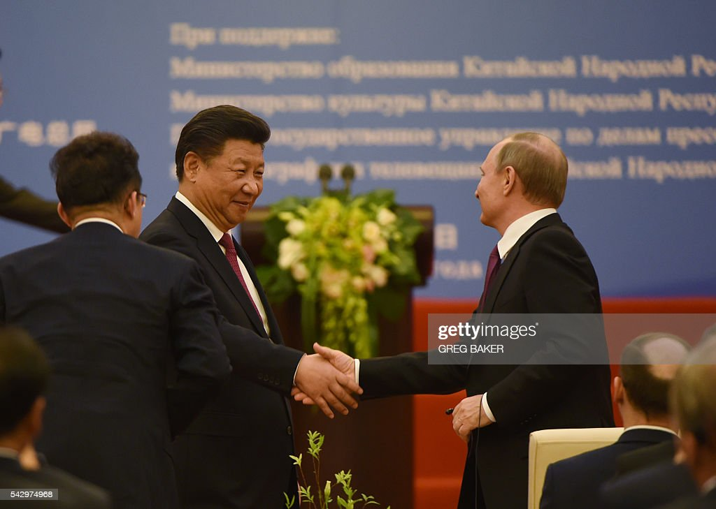Chinese President Xi Jinping (L) shakes hands with Russian President Vladimir Putin during a ceremony marking the 15th anniversary of the signing of the China-Russia Treaty on Good Neighborliness, Friendship and Cooperation, in Beijing's Great Hall of the People on June 25, 2016. / AFP / POOL / GREG