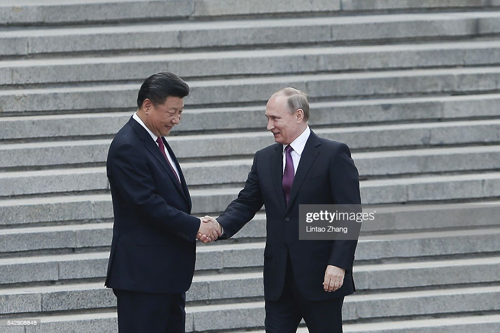 Chinese President <a gi-track='captionPersonalityLinkClicked' href=/galleries/search?phrase=Xi+Jinping&family=editorial&specificpeople=2598986 ng-click='$event.stopPropagation()'>Xi Jinping</a> (L) shakes hands with Russian President <a gi-track='captionPersonalityLinkClicked' href=/galleries/search?phrase=Vladimir+Putin&family=editorial&specificpeople=154896 ng-click='$event.stopPropagation()'>Vladimir Putin</a> (R) before during a welcoming ceremony outside the Great Hall of the People on June 25, 2016 in Beijing, China. At the invitation of President <a gi-track='captionPersonalityLinkClicked' href=/galleries/search?phrase=Xi+Jinping&family=editorial&specificpeople=2598986 ng-click='$event.stopPropagation()'>Xi Jinping</a>, Russian President <a gi-track='captionPersonalityLinkClicked' href=/galleries/search?phrase=Vladimir+Putin&family=editorial&specificpeople=154896 ng-click='$event.stopPropagation()'>Vladimir Putin</a> is in China to discuss more economic and military cooperation between the two countries.