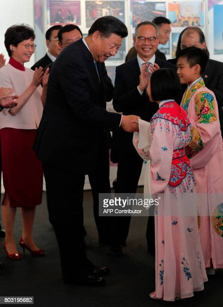Chinese president Xi Jinping shakes hands with two young Chinese opera performers during a visit to Hong Kong's West Kowloon district on June 29 the...