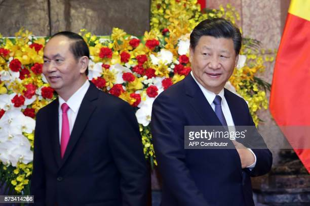 Chinese President Xi Jinping shakes hands with Vietnamese President Tran Dai Quang walks to their seats for a meeting at Presidential Palace in Hanoi...