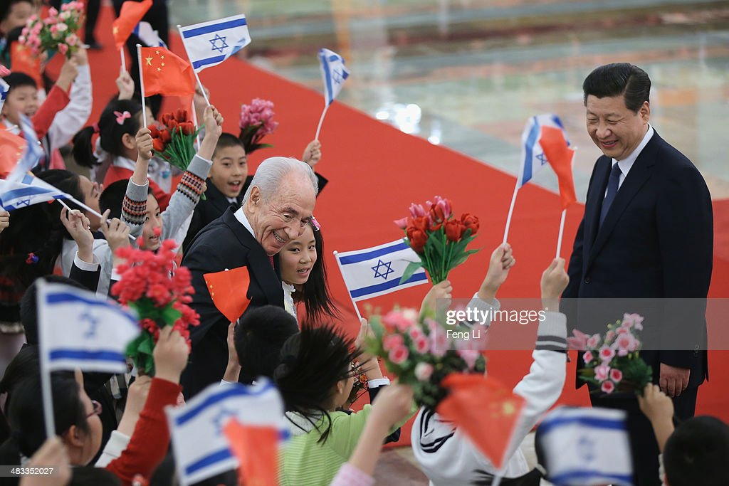 Chinese President Xi Jinping (Right) smiles as Israeli President Shimon Peres (Center) hugs Chinese children after a welcoming ceremony at the Great Hall of the People on April 8, 2014 in Beijing, China. At the invitation of President Xi Jinping, Israeli President Shimon Peres will pay a state visit to China from April 8 to 10.