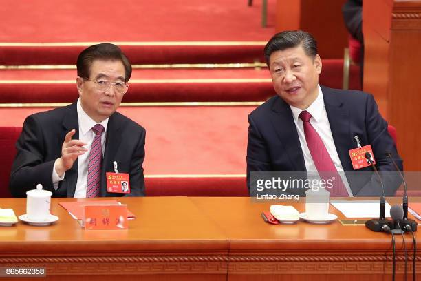 Chinese President Xi Jinping talk with China's former president Hu Jintao during the closing of the 19th Communist Party Congress at the Great Hall...