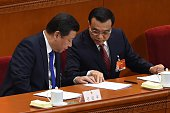 Chinese President Xi Jinping talks to Chinese Premier Li Keqiang at the opening of the 3rd Session of the 12th National People's Congress at the...