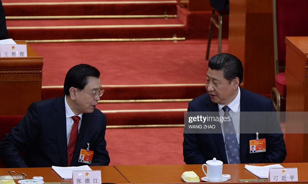 Chinese President Xi Jinping (R) talks to Zhang Dejiang, chairman of the Standing Committee of the National People's Congress (NPC), during the third session of the12th National People's Congress at the Great Hall of the People in Beijing on March 8, 2015. China's Communist Party-controlled legislature, the National People's Congress (NPC), gathers in the capital for the annual show of political theater, with the 'rule of law' high on the agenda. AFP PHOTO / WANG ZHAO