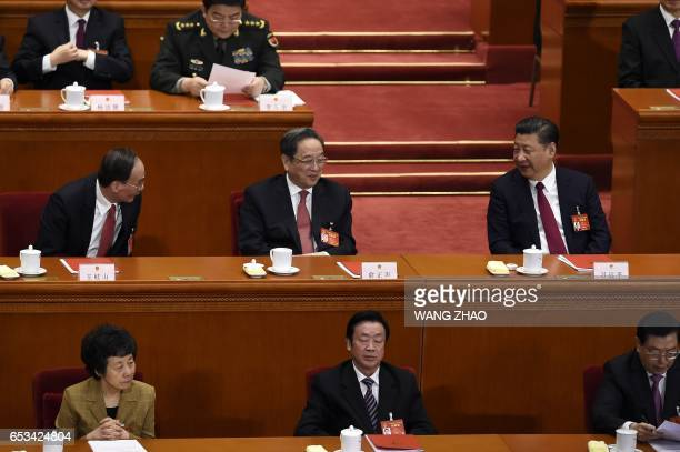 Chinese President Xi Jinping talks with Wang Qishan a member of the Standing Committee of the Political Bureau of the Communist Party of China...
