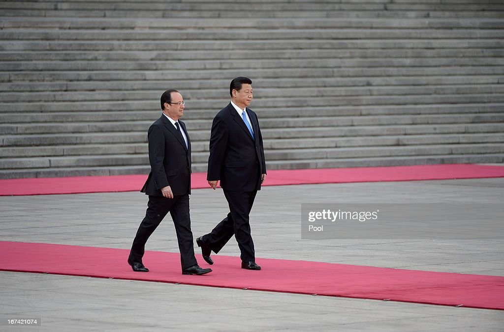 Chinese President Xi Jinping (R) walks a red carpet with French President Francois Hollande during a welcoming ceremony outside the Great Hall of the People on April 25, 2013 in Beijing, China. Hollande has begun a two day trade visit to China bringing with him a large French trade delegation.