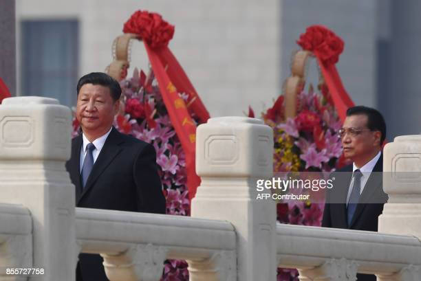 Chinese President Xi Jinping walks with Premier Li Keqiang after laying a wreath at the Monument to the People's Heroes in Tiananmen Square to mark...