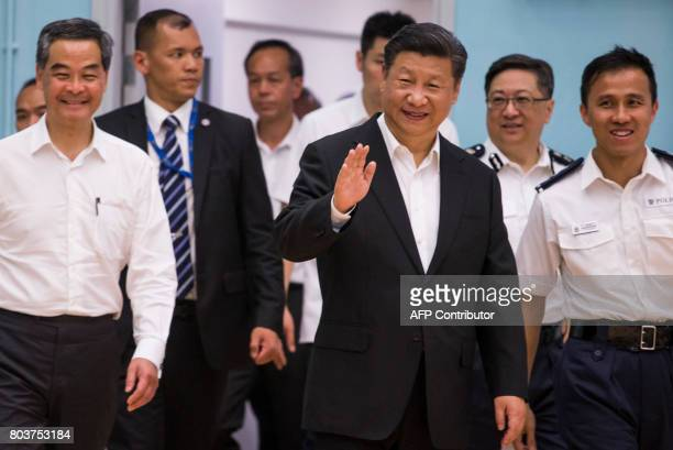 Chinese President Xi Jinping waves as he arrives with outgoing Hong Kong Chief Executive Leung Chunying looks on during a visit at the Hong Kong...