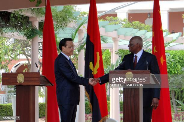 Chinese Prime minister Li Keqiang and Angolan President Jose Eduardo dos Santos shake hands on May 9 2014 in the gardens of the Angolan presidential...