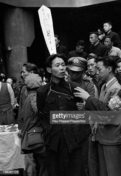 A Chinese prisoner with his hands tied behind his back and his crimes described on a white paper pennant awaits his execution for economic...