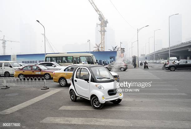 A Chinese produced electric car is driven a street on a heavily polluted day in Beijing on December 8 2015 Half of Beijing's private cars were...