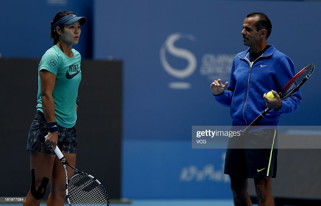 Chinese professional tennis player Li Na looks on as her coach Carlos Rodriguez speaks during a training session ahead of the 2013 China Open at...