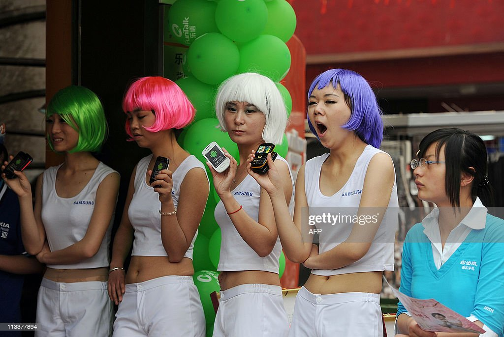 Chinese promoters wear colourful wigs to attract customers to a telecommunication shop for a May Day sales promotion in Hefei east China's Anhui...