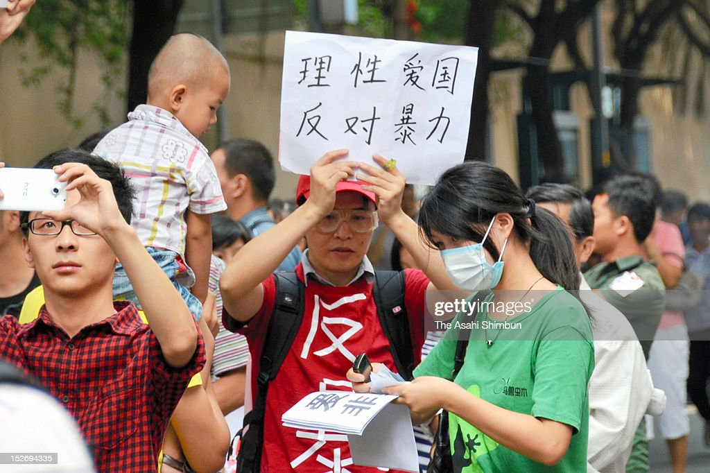 A Chinese protestor holds the banner to call for no violence during an anti Japan rally on September 18, 2012 in Shanghai, China. There were protests in many major cities in China, including Shanghai, Shenzhen, Shenyang, Hangzhou, Harbin, Qingdao and Hong Kong as they oppose to the Japanese government's purchase of the disputed Senkaku/Diaoyu islands.
