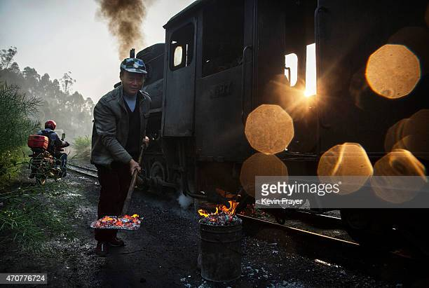BEIJING CHINA Marh 29 A Chinese railway worker removes coal from the tracks as a coal powered steam train dumps coal at a small station on March 29...