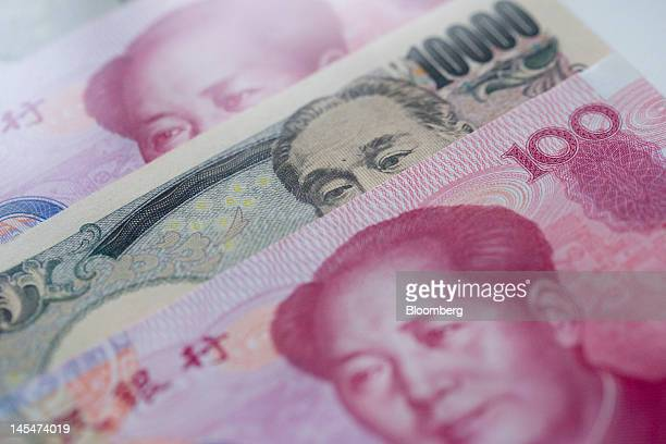 Chinese renminbi and Japanese yen bank notes are arranged for a photograph in Beijing China on Thursday May 31 2012 China and Japan have agreed to...