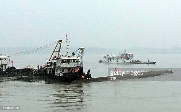 Chinese rescue boats are seen alongside a capsized passenger ship carrying more than 450 people which sunk in the Yangtze river triggering a rescue...