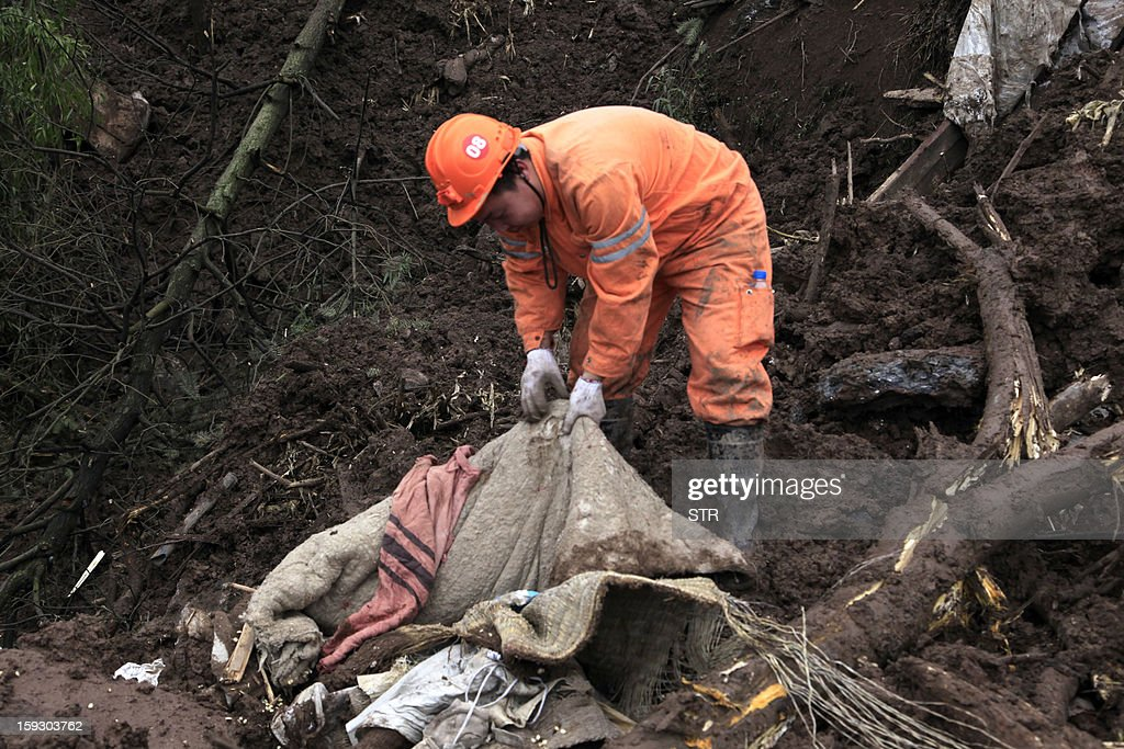 A Chinese rescue worker searches for buried residents in a disaster-hit area in Gaopo village, southwest China's Yunnan province on January 11, 2013. A landslide killed at least 36 people including seven from a single family when it smashed into the village on January 11, state-run media said. CHINA OUT AFP PHOTO