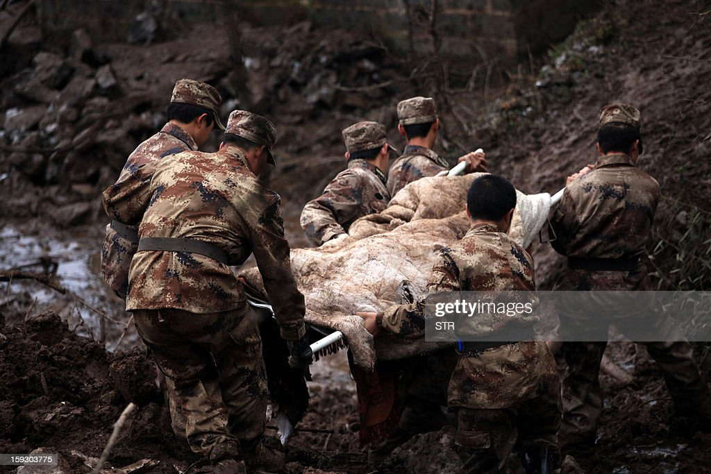 Chinese rescue workers carry a dead body they found while searching for buried residents in a disaster-hit area in Gaopo village, southwest China's Yunnan province on January 11, 2013. A landslide killed at least 36 people including seven from a single family when it smashed into the village on January 11, state-run media said. CHINA