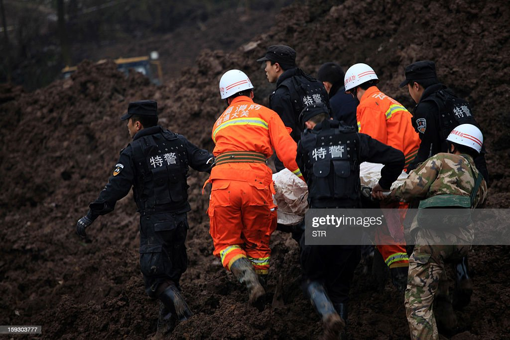 Chinese rescue workers carry a dead body they found while searching for buried residents in a disaster-hit area in Gaopo village, southwest China's Yunnan province on January 11, 2013. A landslide killed at least 36 people including seven from a single family when it smashed into the village on January 11, state-run media said. CHINA OUT AFP PHOTO