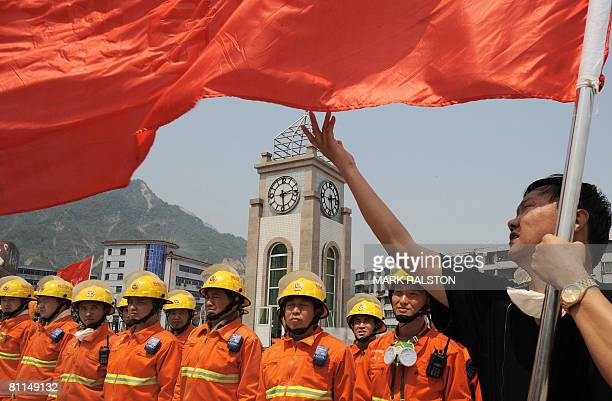 Chinese rescue workers line up behind a flag as they prepare to observe three minutes of silence on May 19 2008 in front of the damaged town clock...