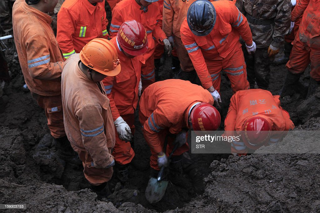 Chinese rescue workers search for buried residents in a disaster-hit area in Gaopo village, southwest China's Yunnan province on January 11, 2013. A landslide killed at least 36 people including seven from a single family when it smashed into the village on January 11, state-run media said. CHINA
