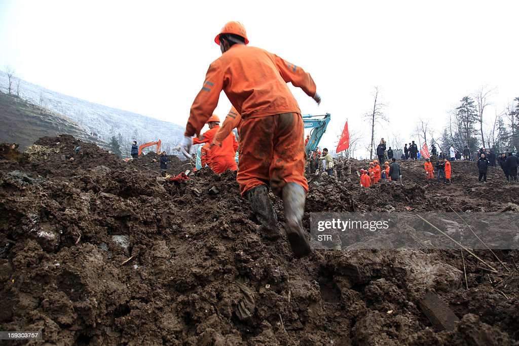 A Chinese rescue workers search for buried residents in a disaster-hit area in Gaopo village, southwest China's Yunnan province on January 11, 2013. A landslide killed at least 36 people including seven from a single family when it smashed into the village on January 11, state-run media said. CHINA OUT AFP PHOTO