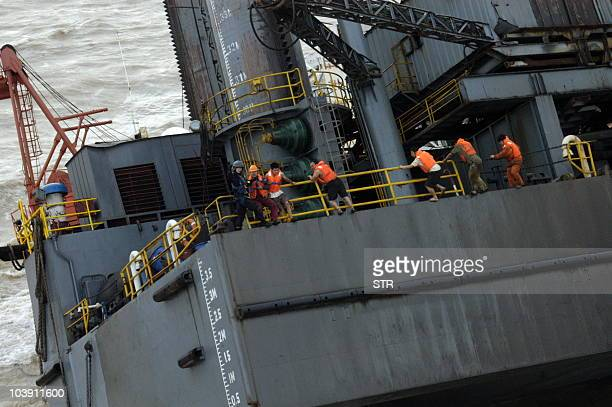 A Chinese rescuer prepares to help airlift the crew off the damaged oil rig on the Shengli oil field off Dongying in northeast China's Shandong...