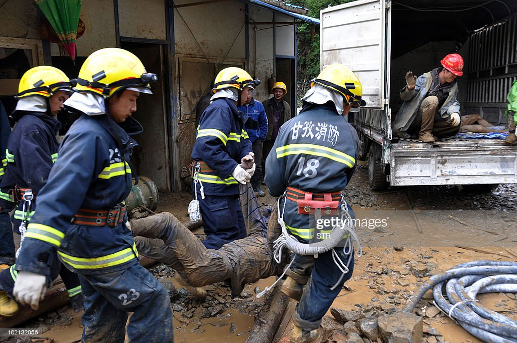 Chinese rescuers remove the bodies of victims killed by a landslide in Kangding, southwest China's Sichuan province on June 15, 2010. Landslides triggered by heavy rain have left at least 24 people dead and another 23 people missing when part of a mountain cascaded down onto a construction site in Sichuan province's Kangding county, slamming into tents where the victims were sleeping. CHINA