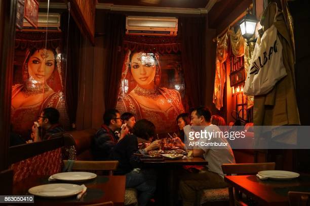 Chinese residents eat dinner at an Indian restaurant as they celebrate the Diwali Festival in Shanghai on October 19 2017 Diwali the Hindu festival...