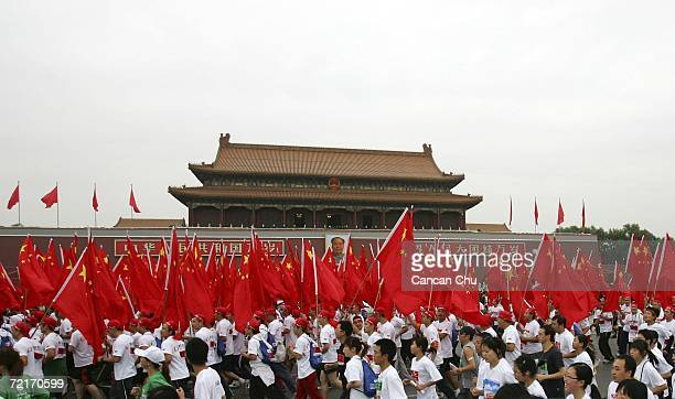 Chinese residents holding Chinese national flags run past the Tiananmen Gate during the 2006 ANA Beijing International Marathon October 15 2006 in...