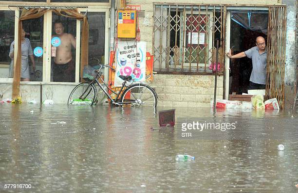 Chinese residents look at a flooded area caused by heavy rain in Beijing on July 20 2016 At least one person was killed and 34 missing as torrential...