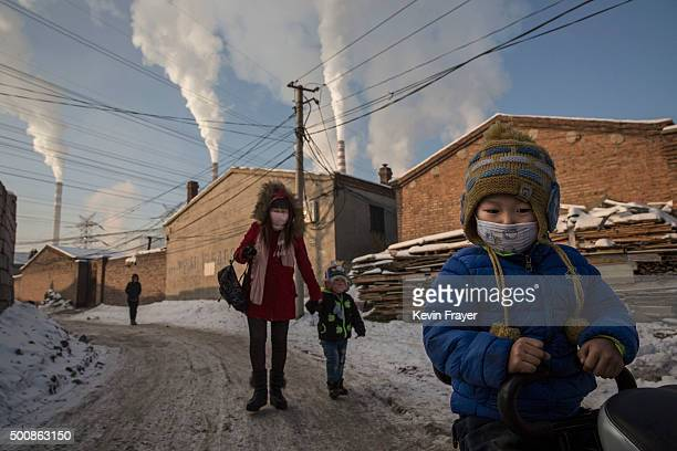 Chinese residents wear masks for protection as smoke billows from stacks in a neighborhood next to a coal fired power plant on November 26 2015 in...