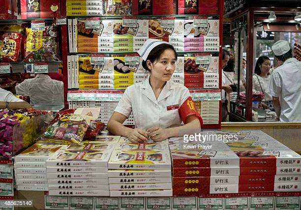 Chinese retail clerk waits for customers at a shop on August 28 2015 in Beijing China China's government is relying on domestic consumption and...