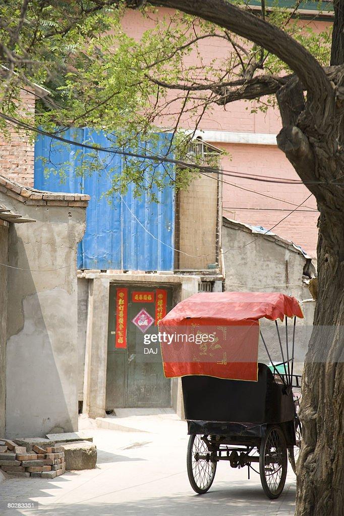 Chinese rickshaw under tree, China, Beijing, Hutong