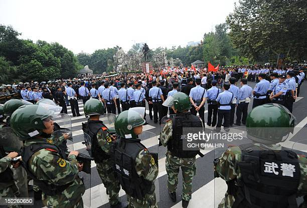 Chinese riot police hold back a group of protesters gathered in front of a monument to soldiers who died in the antiJapan war in Chengdu in southwest...