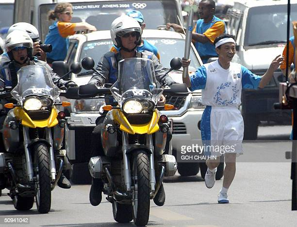 Chinese runner carries the Olympic flame escorted by outriders along a street in Beijing 09 June 2004 during the Beijing leg of the Olympic flame...