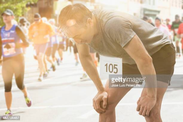 Chinese runner resting at finish line