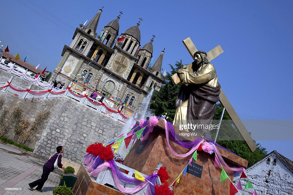 Chinese rural Catholic prays beside a Jesus Cross statue outside a church at Paowo village on May 3 2013 in Baoji China The Shizishan Mountain...