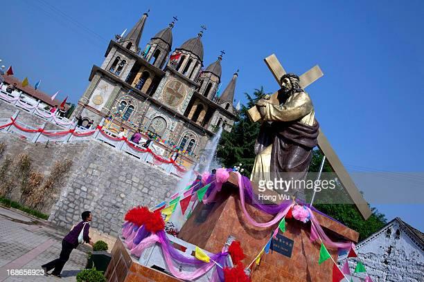 Chinese rural Catholic prays beside a Jesus Cross statue outside a church at Paowo village on May 3 2013 in Baoji China The Shizishan Mountain...